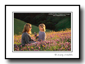 Mom and daughter in spring flower field in green grass hill