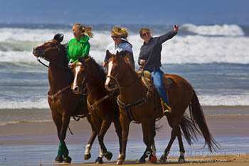 Girls riding horses on beach