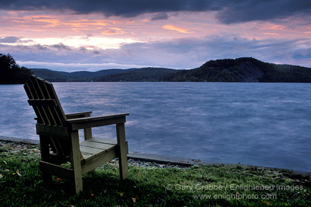 Wooden deck chair and storm clouds at sunset over Lake Bomoseen, near Rutland, Berkshire region, Vermont