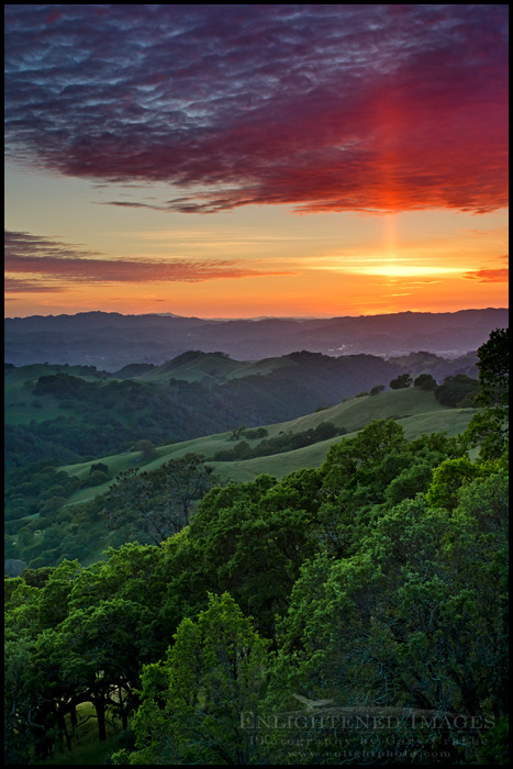 Image:  Sun Pillar at sunset over rolling green hills in Spring, from Mount Diablo State Park, California