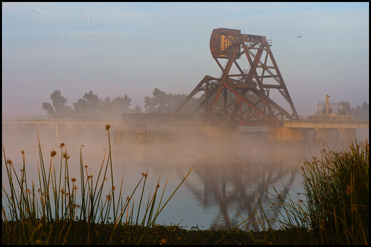 Image: A railroad trestle and counter-weighted draw bridge in the the Sacramento - San Joaquin River Delta at sunrise, California