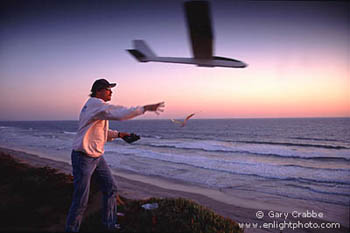 Launching a radio controlled glider into the wind above the Pacific Ocean at sunset, Carlsbad, San Diego County, California Coast